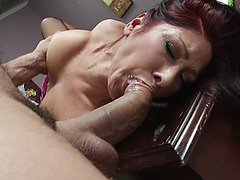 Tiffany Mynx lays on her back with her head hanging off the table as her boss fucks her throat